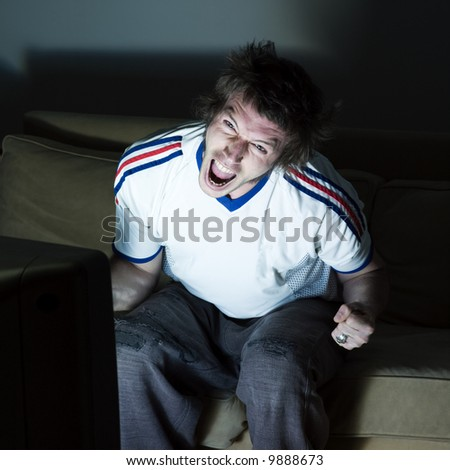 pictures in a living room a funny and expresive man sitting on a couch  watching on tv  sport event - stock photo
