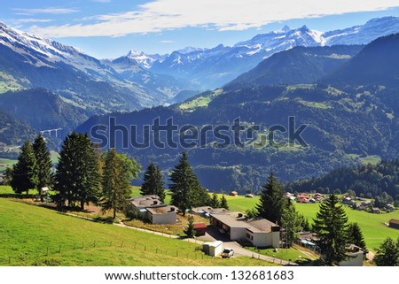 Picturesque gentle alpine meadows and rural houses chalets with red roofs. Gorgeous weather in the resort town of Leysin in the Swiss Alps - stock photo
