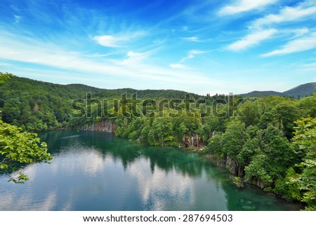 picturesque lake in forest high in mountains - stock photo