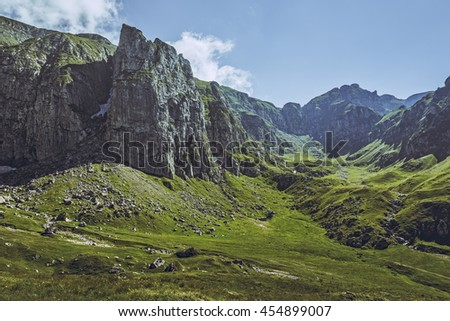 Picturesque mountain landscape with vast green alpine grasslands and steep rocky cliffs in the Malaiesti Valley in Bucegi mountains, Romania. Romanian travel destinations, touristic attractions. - stock photo