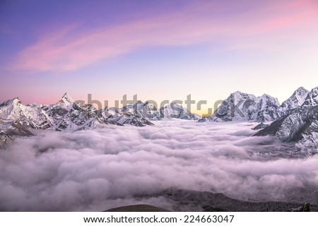 Picturesque mountain valley filled with curly clouds at sunrise. The sacred Ama Dablam peak (6814 m) dominates on the left. Nepal, Himalayas. Canon5D MkII. - stock photo