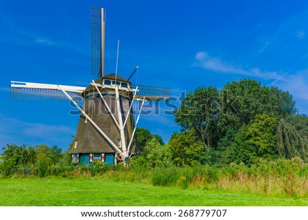 Picturesque rural landscape with windmill Riekermolen in Amsterdam, Holland, Netherlands - stock photo