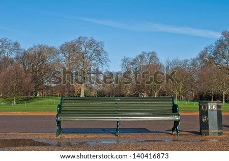 picturesque scene with wooden green bench and litter in Hyde Park, London, England - stock photo