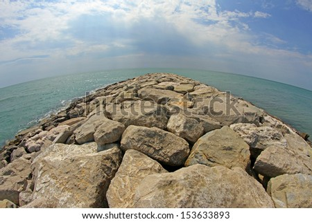 picturesque seaside rocks and breakwaters photographed with the fisheye lens - stock photo
