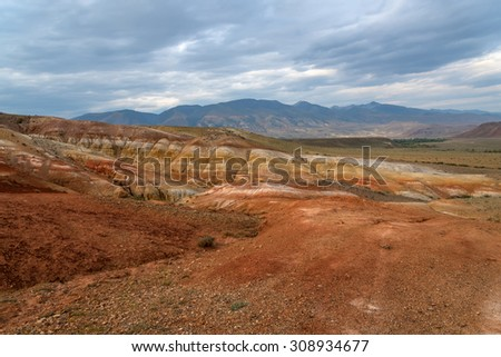 Picturesque steppe desert landscape with multicolored mountains, cracks in the ground and sparse vegetation on the background of cloudy sky - stock photo