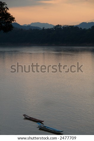 picturesque sunset on the mekong river in laos luangprabang - stock photo