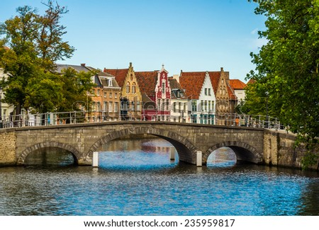 Picturesque view across a bridge to historic brickwall town houses in the famous belgian city of Brugge. - stock photo