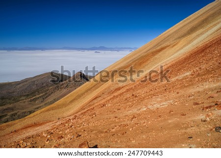 Picturesque view of vast white salt plane Salar de Uyuni from colored mountains - stock photo