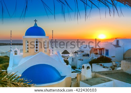 Picturesque view, Old Town of Oia or Ia on the island Santorini, white houses and church with blue domes at sunset, Greece - stock photo