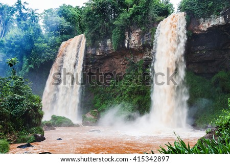 Picturesque waterfall falls over mossy rocks in forest - stock photo