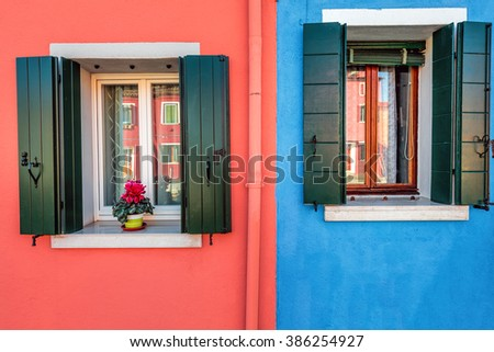 Picturesque window with blue house reflection on yellow wall of houses on the famous island Burano, Venice, Italy - stock photo