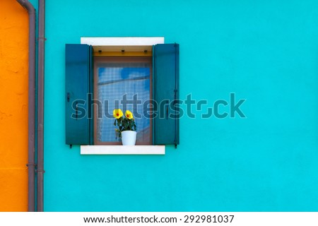 Picturesque windows with shutters and flowers on blue and orange wall of houses on the famous island Burano, Venice, Italy - stock photo