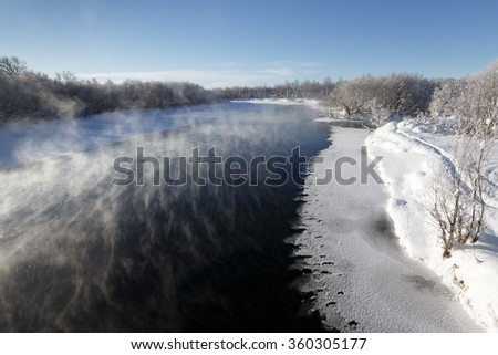 Picturesque winter landscape: view of the Kamchatka River (largest river on the Kamchatka Peninsula) on a sunny frosty day. Eurasia, Russian Far East, Kamchatka Krai. - stock photo