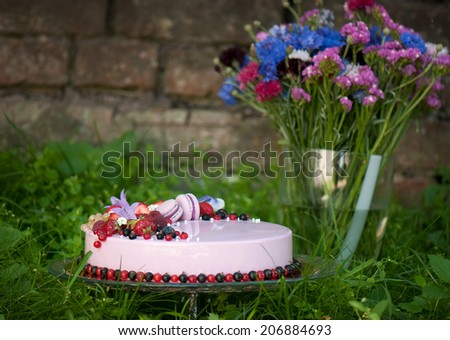 Pie decorated with fresh berries against a grass and flowers - stock photo