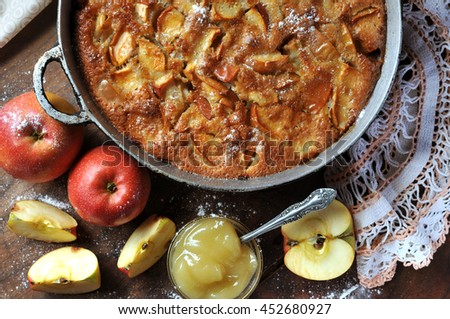 Pie with apples.Pie, apple, apple slices and honey on the wooden table. - stock photo