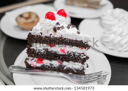 piece of a black forest cake with meringue and egg tart on the background - stock photo