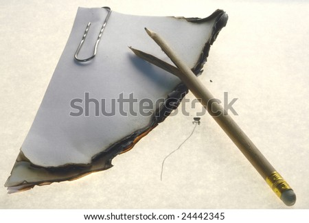 Piece of a burnt paper and the broken pencil isolated on a white background - stock photo
