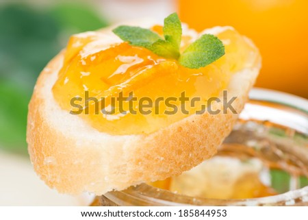 piece of baguette with orange marmalade, close-up, horizontal - stock photo