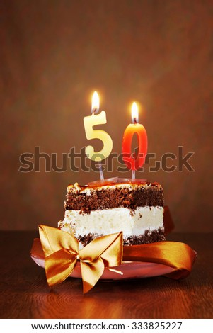 Piece of Birthday Chocolate Cake with Burning Candle as a Number Fifty on Brown Background - stock photo