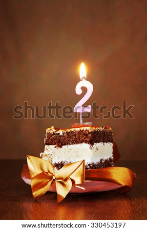 Piece of Birthday Chocolate Cake with Burning Candle as a Number Two on Brown Background - stock photo