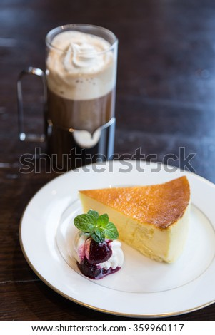 Piece of blueberry cheesecake and coffee latte on the table - stock photo