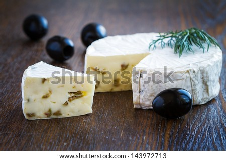 Piece of Brie Cream Cheese with olives - stock photo