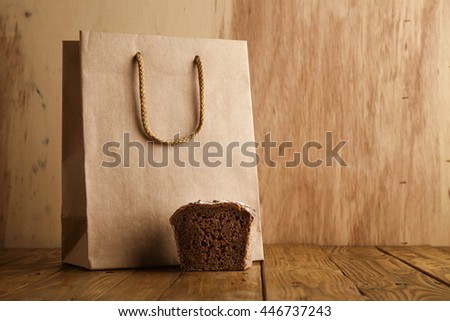 Piece of brown rye bread presented near take away blank bag from craft paper in artisan bakery on wooden background - stock photo