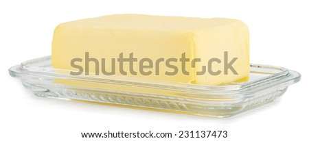 Piece of butter on glass butter dish over white background. - stock photo