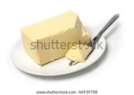 Piece of butter on white plate with knife. White background and shallow focus. - stock photo