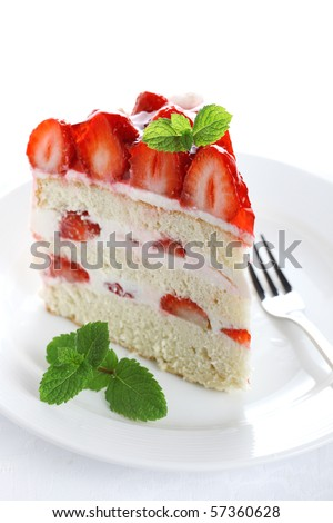 piece of cake on white plate with strawberries - stock photo