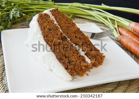 Piece of carrot cake with fresh carrots - stock photo