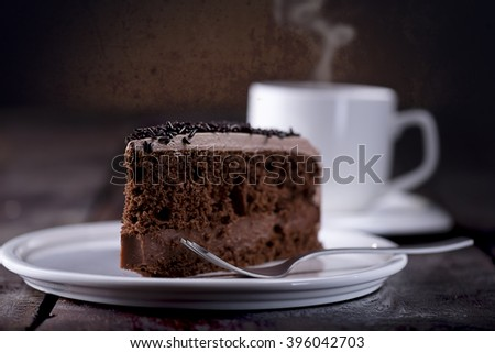 Piece of chocolate cake and a fork on the right side. A Cup of hot coffee with steam in the background. View from right Front - stock photo