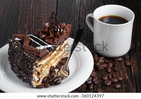 Piece of chocolate cake and cup of coffee on dark wooden table - stock photo