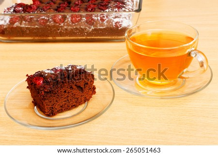 Piece of chocolate cake with cherry and cup of tea - stock photo
