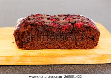 Piece of chocolate cake with cherry on the table - stock photo