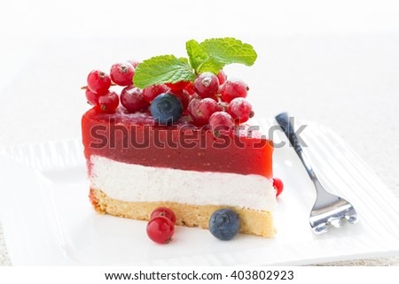 piece of delicious cheesecake with berry jelly on a white plate, close-up - stock photo