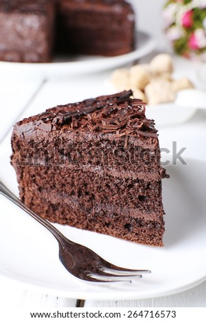 Piece of delicious chocolate cake in plate with fork on color wooden table background - stock photo