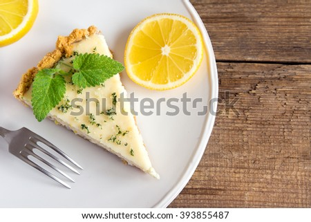 Piece of delicious homemade lemon cheesecake with mint close up - stock photo