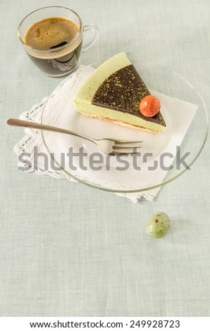 Piece of easter cake with tea matcha decorated chocolate ganache and sweet-stuff eggs on glass plate.  - stock photo