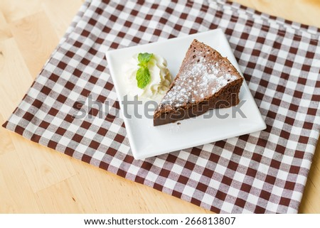 piece of flourless chocolate cake on white square dish - stock photo