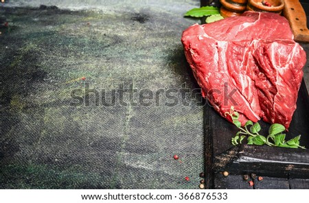 Piece of fresh raw beef meat with seasoning and herbs  on rustic background , top view, place for text - stock photo