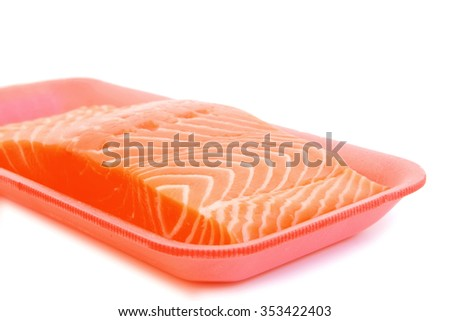 piece of fresh raw salmon on red tray isolated on white background . shallow dof - stock photo