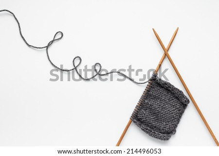 Piece of grey knitting on knitting needles - stock photo