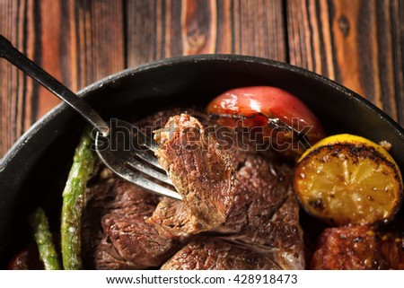 Piece of grilled beef steak on fork with vegetables with vegetables in the pan  - stock photo