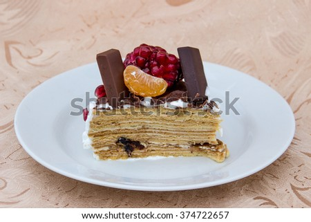 piece of honey cake with fruit, prunes and chocolate - stock photo