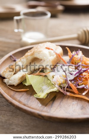 piece of Hotdog remains on wooden plate, food scraps - stock photo