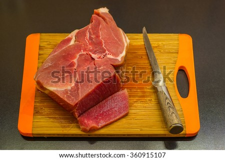 Piece of meat and knife and cutting board  - stock photo