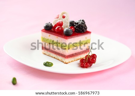 Piece of Multi-layered Berry and Pistachio Mousse Cake, on a white plate and on light pink background. - stock photo