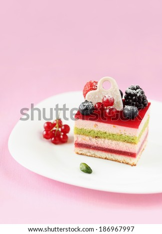 Piece of Multi-layered Berry and Pistachio Mousse Cake, on a white plate, on a light pink background. - stock photo