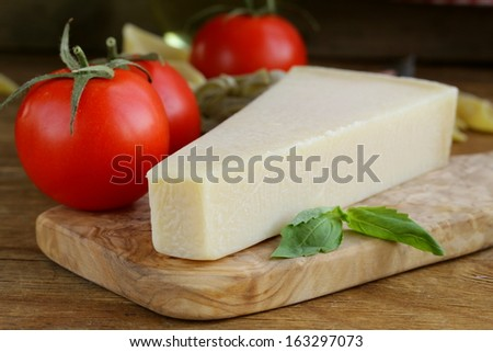 piece of natural parmesan cheese on a wooden board - stock photo